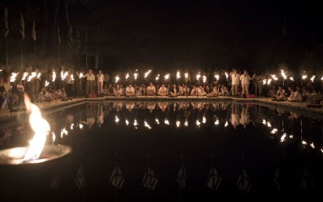 Israeli scouts of the Modiin Tribe light torches during a ceremony commemorating the fallen Israeli soldiers, on the eve of the Israeli Memorial Day at the Mount Herzl military cemetery in Jerusalem, on April 30, 2017. (Yonatan Sindel/Flash90)