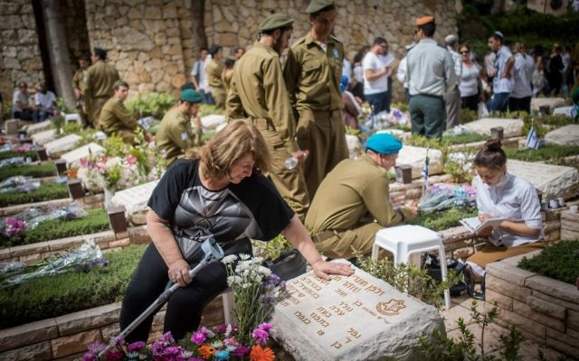 Bereaved Israelis mourn next to graves of fallen soldiers at the Mount Herzl military cemetery in Jerusalem, during Israeli Memorial Day, May 1, 2017. (Yonatan Sindel/Flash90)