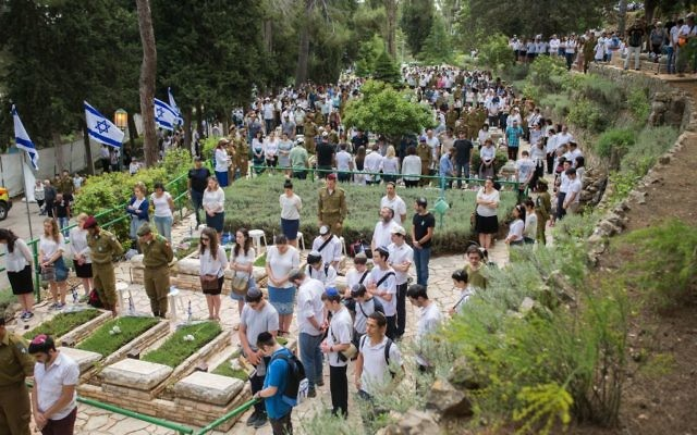 Israelis stand still in silence next to graves of soldiers at the Mt Herzl miitary cemetery in Jerusalem, as a two minute siren sounded across Israel, marking Memorial Day which commemorates Israel's fallen soldiers and victims of terror. May 1, 2017. (Yonatan Sindel/Flash90)