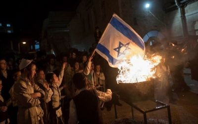Ultra-Orthodox Jews burn an Israeli flag during Lag B'Omer celebrations in the ultra-Orthodox neighborhood of Mea She'arim in Jerusalem, on May 13, 2017. (Noam Revkin Fenton/Flash90)