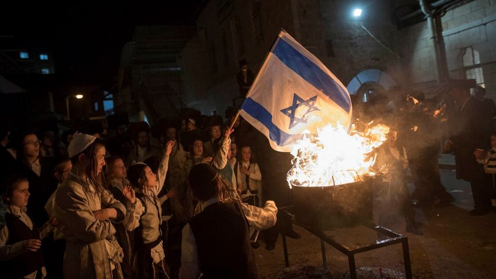 Ultra-Orthodox Jews burn an Israeli flag during Lag B'Omer celebrations in the ultra-orthodox neighborhood of Mea She'arim in Jerusalem on May 13, 2017. (Noam Revkin Fenton/Flash90)