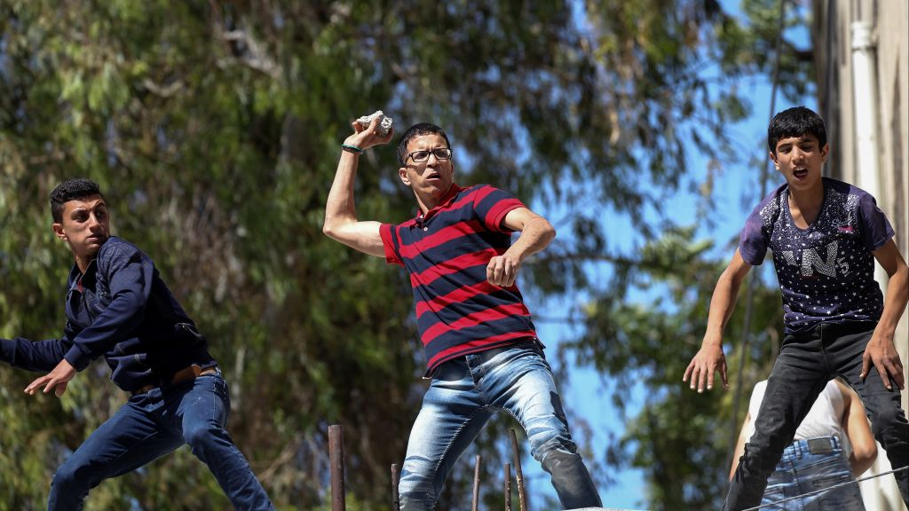 Palestinians throw stones at Israeli troops during clashes in the West Bank city of Hebron, May 26, 2017. Demonstrators protested in solidarity with Palestinian prisoners in Israeli jails. (Wisam Hashlamoun/Flash90)