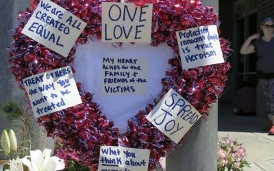 A heart-shaped wreath covered with positive messages hangs on a traffic light pole at a memorial for two bystanders who were stabbed to death trying to stop a man who was yelling anti-Muslim slurs on a light-trail train in Portland, Oregon on May 27, 2017. (AP Photo/Gillian Flaccus)