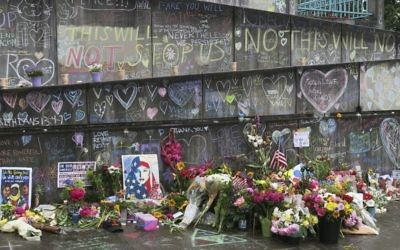 Flowers, candles and chalk tributes are seen on Tuesday, May 30, 2017, covering a memorial to two men who were fatally stabbed after shielding two young women from an anti-Muslim tirade on a Portland, Ore., light-rail train. (AP /Gillian Flaccus)