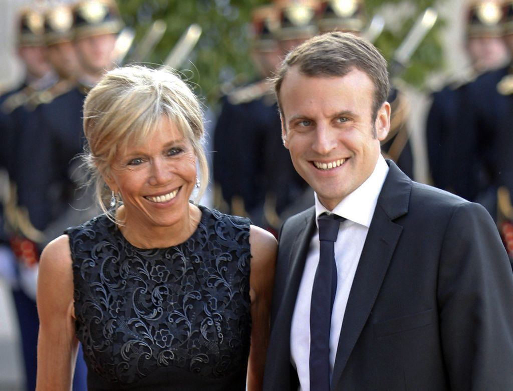 FILE - In this file photo dated Tuesday, June 2, 2015, France's Economy Minister Emmanuel Macron and his wife Brigitte Trogneux pose for photographers as they arrive at the Elysee Palace in Paris, France. (Jacques Brinon/AP)