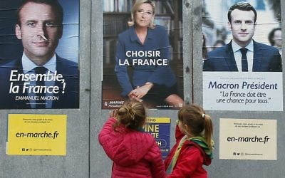 Children walk past election campaign posters for French centrist presidential candidate Emmanuel Macron and far-right candidate Marine Le Pen, in Osses, southwestern France, Friday May 5, 2017. (AP Photo/Bob Edme)