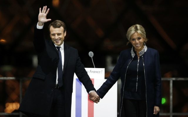 French President-elect Emmanuel Macron holds hands with his wife Brigitte during a victory celebration outside the Louvre museum in Paris, France, Sunday, May 7, 2017. (AP Photo/Thibault Camus)