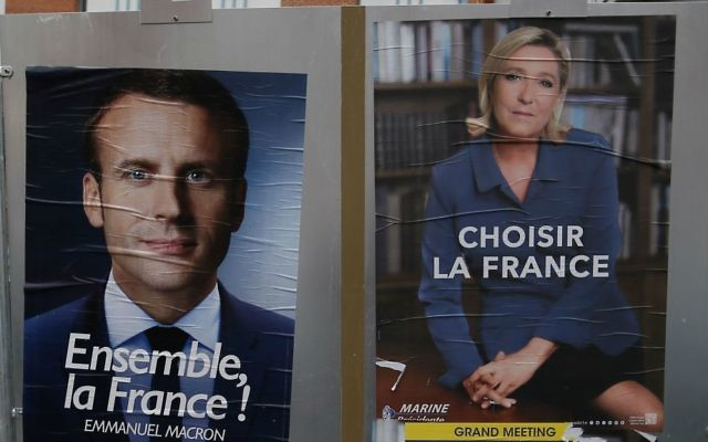 Election campaign posters for French centrist presidential candidate Emmanuel Macron and far-right candidate Marine Le Pen are displayed in front of the polling station where Marine Le Pen will vote in Henin Beaumont, northern France, Saturday, May 6, 2017. (AP Photo/Francois Mori)