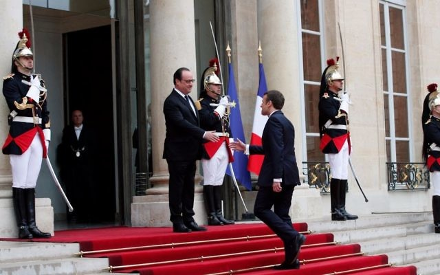 Outgoing French president Francois Hollande, left, greets President Emmanuel Macron before the handover ceremony, at the Elysee Palace in Paris, France, Sunday, May 14, 2017. (AP Photo/Christophe Ena)