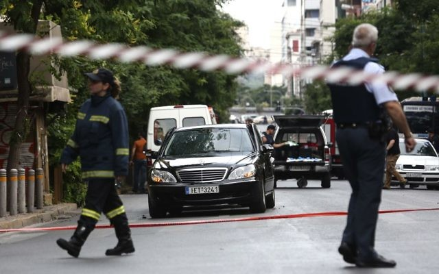 Members of the emergency services walk by a car, near the scene of an explosion, in Athens, Thursday, May 25, 2017. (AP Photo/Yorgos Karahalis)