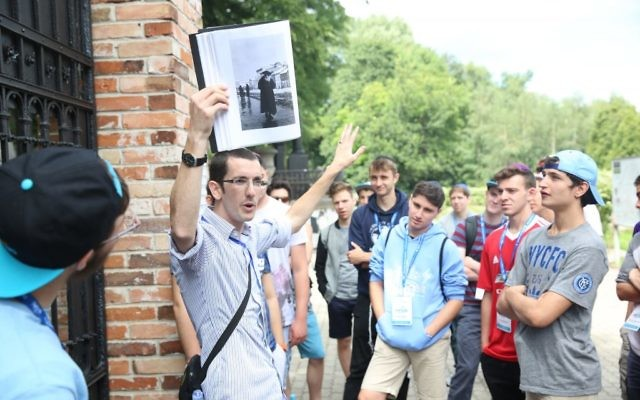JRoots educator Zak Jeffay leading a tour in the Warsaw Jewish Cemetery. (Courtesy)