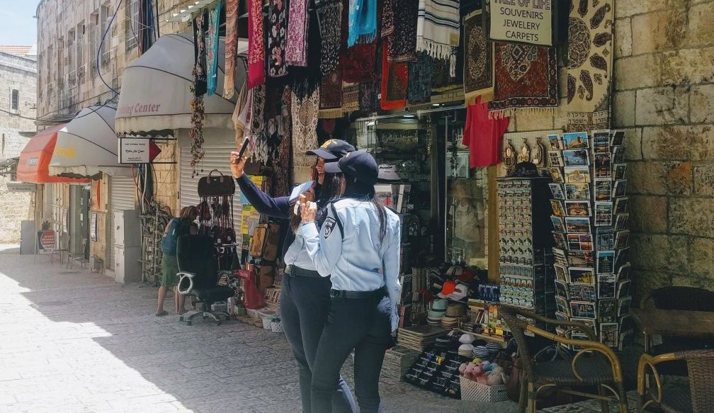 """Two police officers on duty in the Old City's Christian Quarter ahead of the Trump visit take a selfie on May 22, 2017. """"The police hats they sell the tourists are just like ours!"""" one of the policewoman noted. (Melanie Lidman/Times of Israel)"""