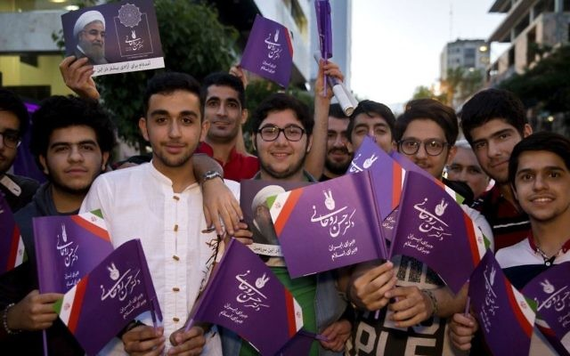 In this Wednesday May 10, 2017 photo, supporters of Iranian President Hassan Rouhani hold his posters for May 19 presidential election in downtown Tehran, Iran. (AP Photo/Ebrahim Noroozi)
