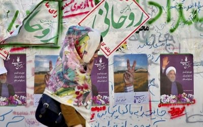 In this Wednesday, May 10, 2017 photo, an Iranian woman walks past electoral posters and hand written slogans for presidential election candidates in downtown Tehran, Iran. (AP Photo/Ebrahim Noroozi)