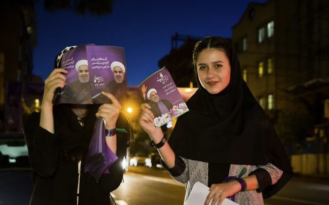 In this May 10, 2017 photo, supporters of Iranian President Hassan Rouhani hold his posters for May 19 presidential election in downtown Tehran, Iran. (AP Photo/Ebrahim Noroozi)