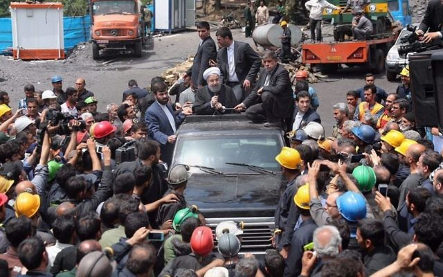 In this photo released by an official website of the office of the Iranian Presidency, Iranian President Hassan Rouhani, center, addresses coal miners during his visit to the site of a deadly mine explosion in Zemestanyourt mine, near Azadshar, northern Iran, Sunday, May 7, 2017. (Iranian Presidency Office via AP)