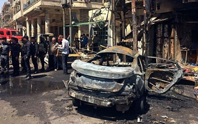 Iraqi security forces and civilians inspect the site of a deadly bomb attack, in Baghdad, Iraq, Monday, May 30, 2017. (AP Photo/Karim Kadim)