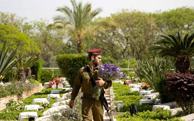 An Israeli soldier holds flowers to be placed on the graves of fallen soldiers on the eve of Israel's Memorial Day at the Kiryat Shaul military cemetery in Tel Aviv, Sunday, April 30, 2017. (AP Photo/Ariel Schalit)