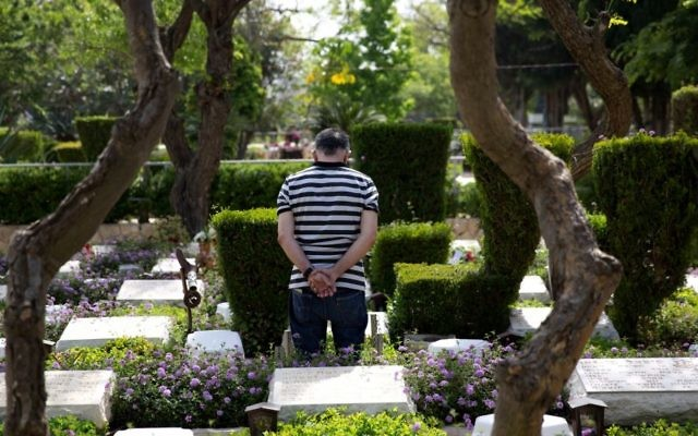 A man stands by the grave of a fallen soldier on the eve of Memorial Day at the Kiryat Shaul military cemetery in Tel Aviv, Sunday, April 30, 2017. (AP Photo/Ariel Schalit)