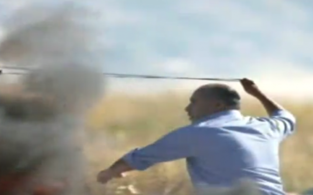 PA lawmaker Jamil Hawil seen throwing rocks at Israeli troops during clashes near the Beit El junction in the West Bank on May 13, 2017. (Screen capture: Channel 2)