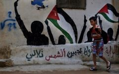 """In this Thursday, May 4, 2017 photo, a boy walks by graffiti of Palestinian flags with Arabic reading: """"The flag is four colors that shine on the face of the sun"""" in the Bourj al-Barajneh Palestinian refugee camp in Beirut, Lebanon. (AP Photo/Bilal Hussein)"""
