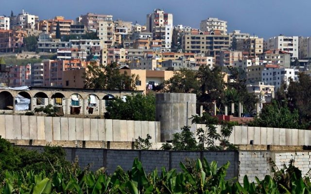 In this Friday, May 5, 2017 photo, a general view of the concrete wall surrounding the Ein el-Hilweh Palestinian refugee camp near the southern port city of Sidon, Lebanon. (AP Photo/Bilal Hussein)