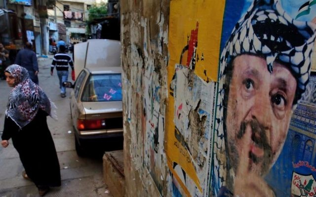 In this Thursday, May 4, 2017 photo, a woman walks past a poster of the late Palestinian leader Yasser Arafat, in the Bourj al-Barajneh Palestinian refugee camp in Beirut, Lebanon. (AP Photo/Bilal Hussein)
