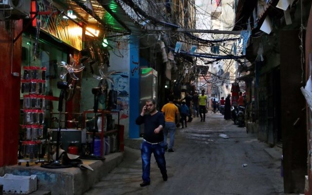 In this Thursday, May 4, 2017 photo, people walk inside the Bourj al-Barajneh Palestinian refugee camp in Beirut, Lebanon. (AP Photo/Bilal Hussein)