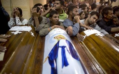 Relatives of Coptic Christians who were killed during a bus attack, surround their coffins, during their funeral service, at Abu Garnous Cathedral in Minya, Egypt, May 26, 2017. (AP Photo/Amr Nabil)
