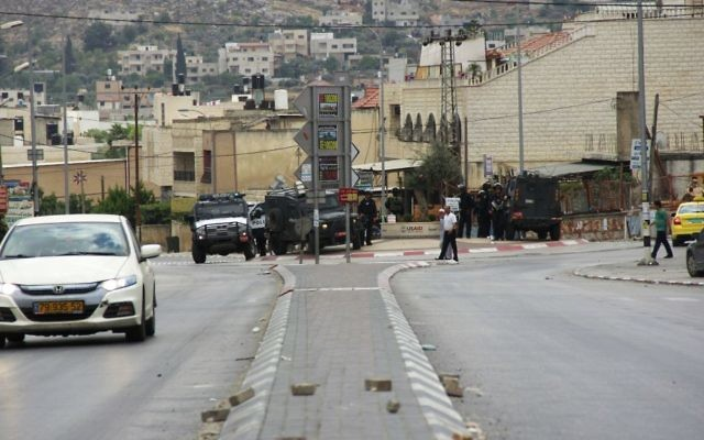 A car drives by the street where a group of Palestinians attacked an Israeli settler, who fired back, killing one person and wounding another, in Hawara, in the northern West Bank on May 19, 2017. (Judah Ari Gross/Times of Israel)