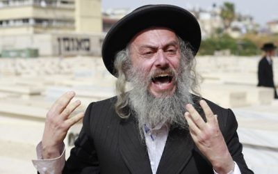 An ultra-Orthodox protester screams at the people attending a ceremony for fallen ultra-Orthodox soldiers at a cemetery in the city of Bnei Brak on May 1, 2017, Israel's Memorial Day. (Judah Ari Gross/Times of Israel)