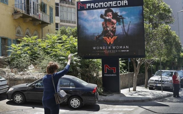 A woman waves for taxi, as she stands in front of a digital billboard promoting the 2017 Wonder Woman movie, in Beirut, Lebanon, Tuesday, May 30, 2017.  (AP Photo/Hussein Malla)