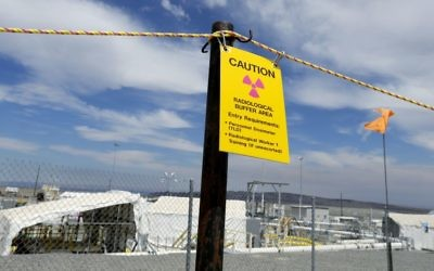 "In this July 9, 2014, file photo, a sign warns of radioactivity near a wind direction flag indicator at the ""C"" tank farm on the Hanford Nuclear Reservation near Richland, Wash. (AP Photo/Ted S. Warren, file)"