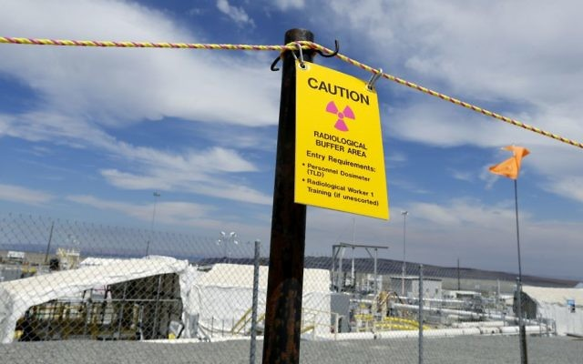 """In this July 9, 2014, file photo, a sign warns of radioactivity near a wind direction flag indicator at the """"C"""" tank farm on the Hanford Nuclear Reservation near Richland, Wash. (AP Photo/Ted S. Warren, file)"""