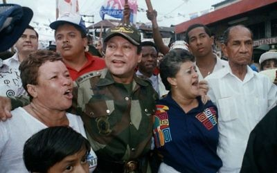 In this May 2, 1989 file photo, Gen. Manuel Antonio Noriega walks with supporters in the Chorrilo neighborhood, where he dedicated a new housing project, in Panama City. (AP/John Hopper, File)