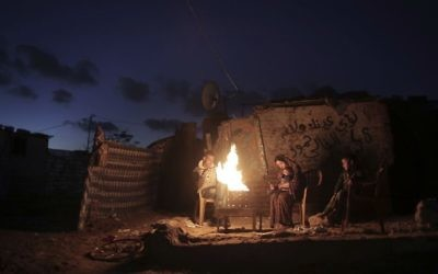 In this Sunday, Jan. 15, 2017 file photo, a Palestinian family warm themselves up with a fire outside their makeshift house during a power cut in a poor neighborhood in town of Khan Younis in the southern Gaza Strip. (AP Photo/ Khalil Hamra, File)