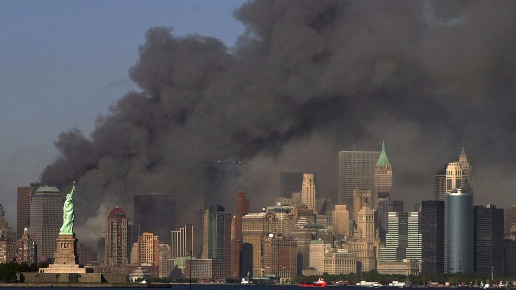In this Sept. 11, 2001 file photo, thick smoke billows into the sky from the area behind the Statue of Liberty, lower left, where the World Trade Center towers stood. (AP Photo/Daniel Hulshizer)