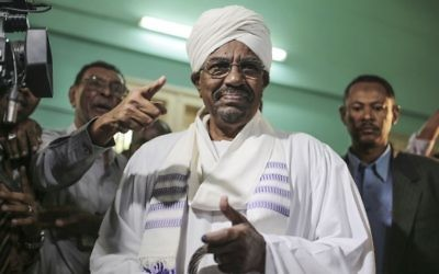 In this Monday, April 13, 2015 file photo, Sudanese President Omar al-Bashir prepares to cast his ballot for the country's presidential and legislative elections in Khartoum, Sudan. (AP Photo/Mosa'ab Elshamy, File)