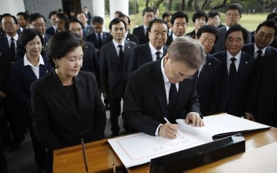 New South Korea's President Moon Jae-in, center, writes down a visitor's book at the National Cemetery in Seoul, South Korea Wednesday, May 10, 2017. (Kim Hong-ji/AP)