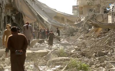 This undated frame grab from video posted online Monday, May 29, 2017, by the Aamaq News Agency, a media arm of the Islamic State group, shows people inspecting damage from airstrikes and artillery shelling in the northern Syrian city of Raqqa, the de facto capital of the IS. (Aamaq News Agency via AP)