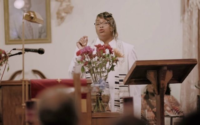 A woman delivering a sermon while draped in a tallit from the documentary '4 Your Eyez Only,' by rapper J. Cole. (Youtube/Dreamville)