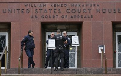 Law enforcement officials stand outside a federal courthouse in Seattle, as a three-judge panel of the 9th US Circuit Court of Appeals hears arguments inside over Hawaii's lawsuit challenging President Donald Trump's revised travel ban, May 15, 2017. (AP/Ted S. Warren)
