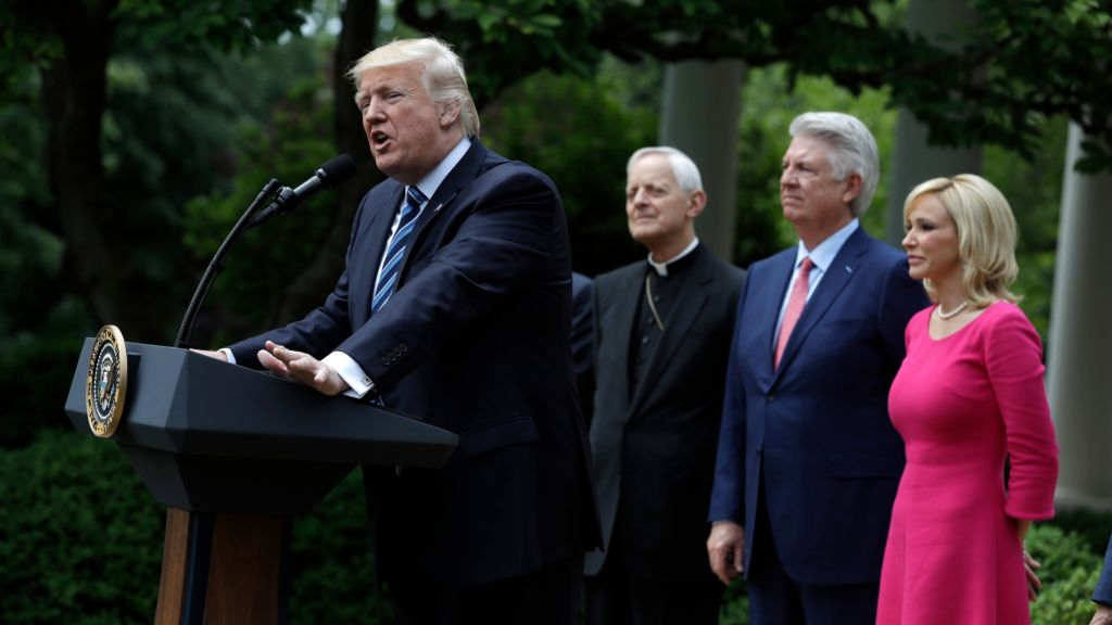US President Donald Trump speaks in the Rose Garden of the White House in Washington, Thursday, May 4, 2017, before signing an executive order aimed at easing an IRS rule limiting political activity for churches. From second from left are, Cardinal Donald Wuerl is the Archbishop of Washington, Pastor Jack Graham, and Paula White, senior pastor of New Destiny Christian Center in Apopka, Fla. (AP Photo/Evan Vucci)