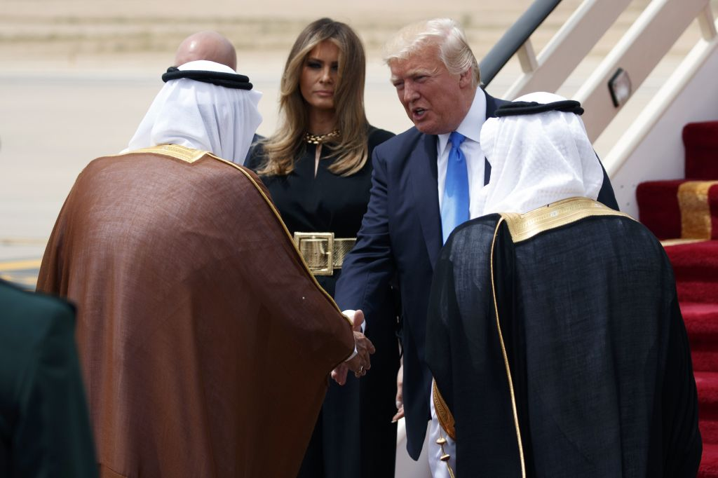 President Donald Trump, top right, accompanied by first lady Melania Trump, center, shakes hands with Saudi King Salman during a welcome ceremony at the Royal Terminal of King Khalid International Airport, Saturday, May 20, 2017, in Riyadh. (AP Photo/Evan Vucci)