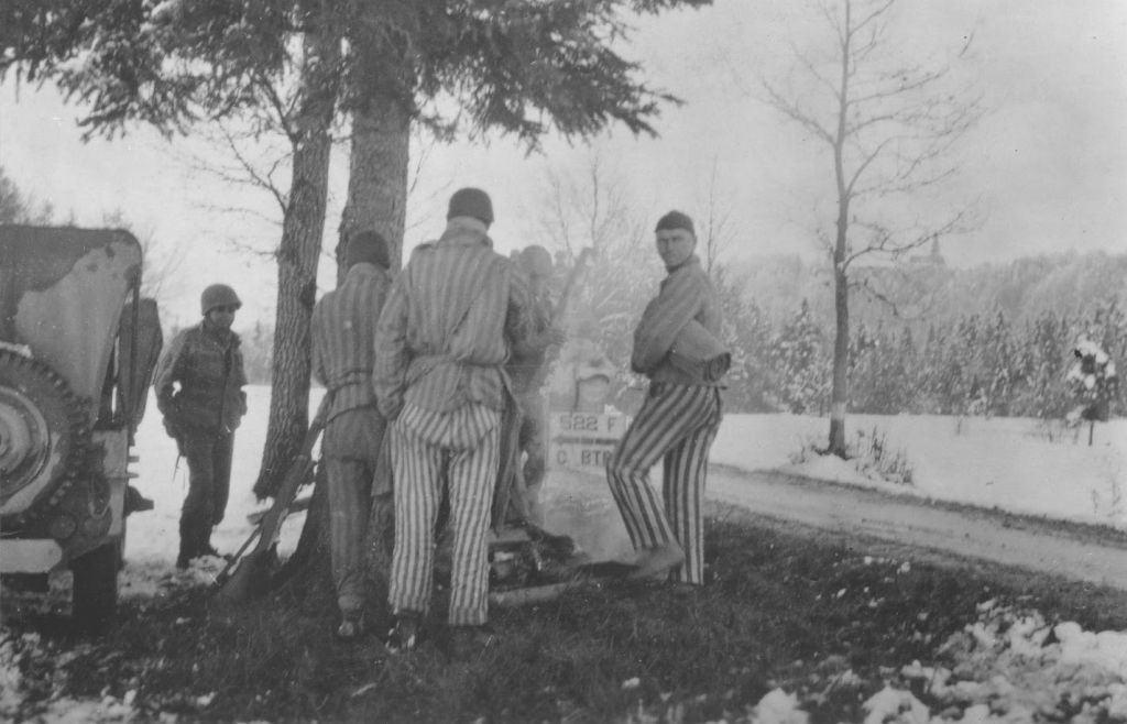 Survivors from a death march from Dachau huddle around a campfire prepared by Japanese-American soldiers with the 522nd Field Artillery Battalion. The soldier on the left is George Oiye. (Courtesy USHMM/Eric Saul)