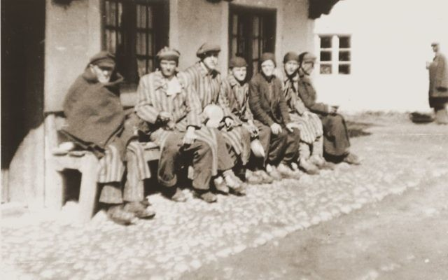A group of concentration camp prisoners who were liberated on a death march from Dachau sit on a bench waiting to receive food from Japanese-American soldiers with the 522nd Field Artillery Battalion. (Courtesy USHMM/Eric Saul)