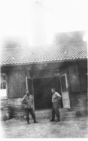 Two Japanese-American soldiers with the 522nd Field Artillery Battalion stand in front of the crematorium in the Dachau concentration camp soon after the liberation. (Courtesy USHMM/Eric Saul)