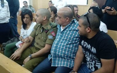 IDF soldier Elor Azaria sits between his parents in a courtroom at the Kirya military headquarters in Tel Aviv for an appeal hearing on Wednesday, May 3, 2017 (Judah Ari Gross/Times of Israel)