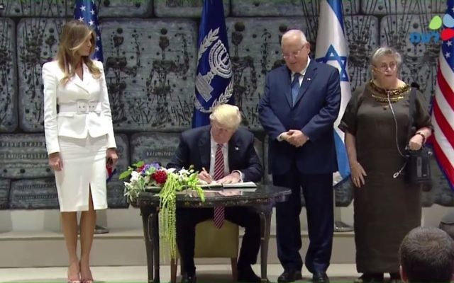 US President Donald Trump signs the guestbook at the official residence of his Israeli counterpart, Reuven Rivlin, who watches on, on Monday, May 22, 2017 (screen capture: GPO)