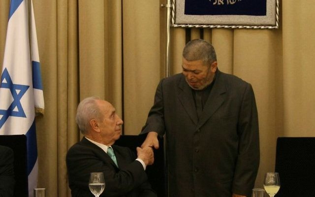 Israel's late president Shimon Peres shakes hands with Sheikh Abdullah Nimr Darwish (R) during an Iftar meal at the President's Residence in Jerusalem on September 9, 2008. (Anna Kaplan/Flash90)